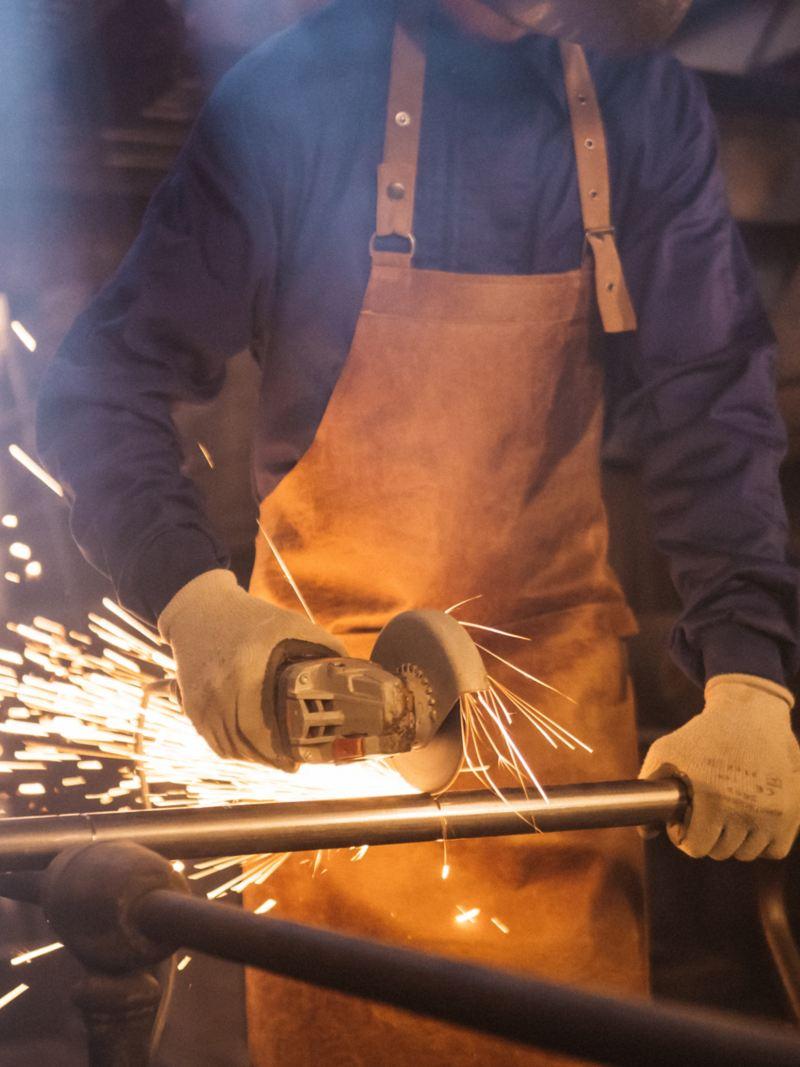 volkswagen profesionales hombre cortando un tubo con una sierra circular