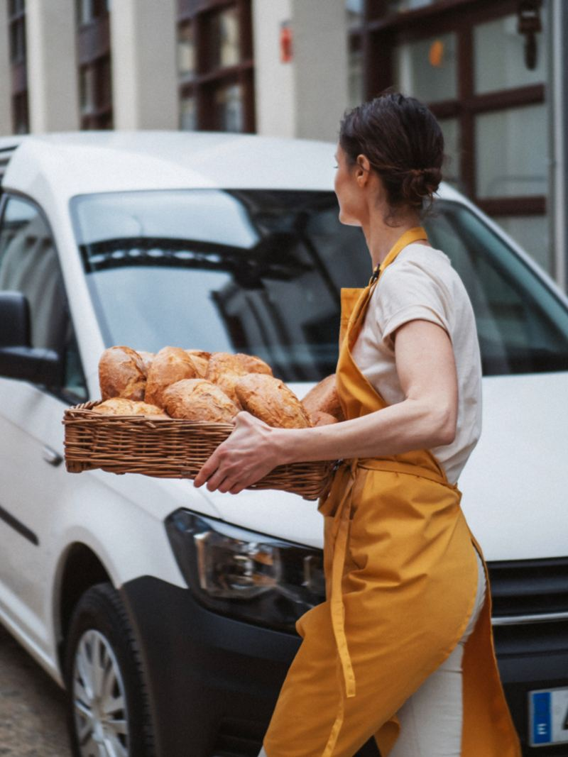 volkswagen profesionales mujer con una cesta de pan delante de un furgon
