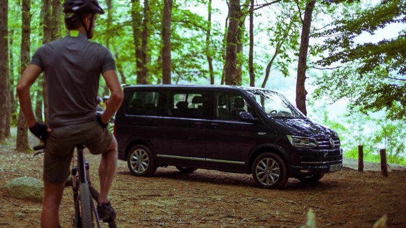 hombre en bicicleta delante de un volkswagen multivan en el bosque