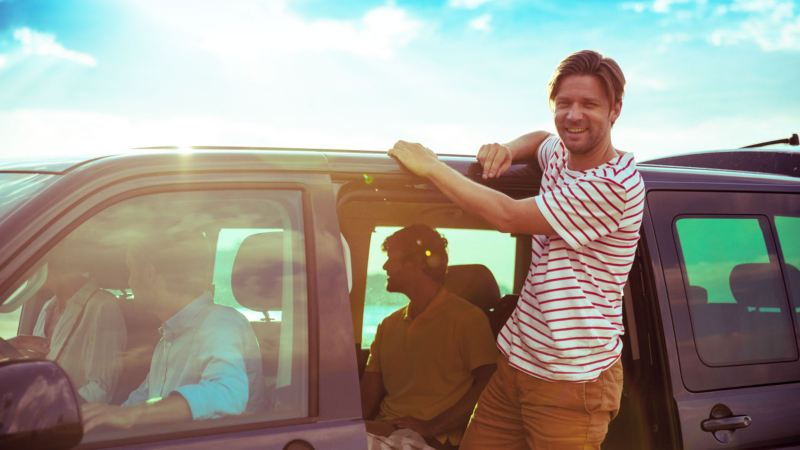 Hombre joven subido por la puerta lateral a un furgón Volkswagen