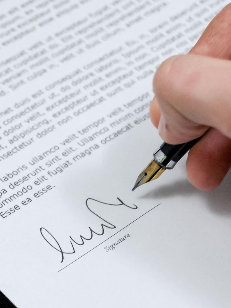 Ein Hand setzt eine Unterschrift unter einen Vertrag.