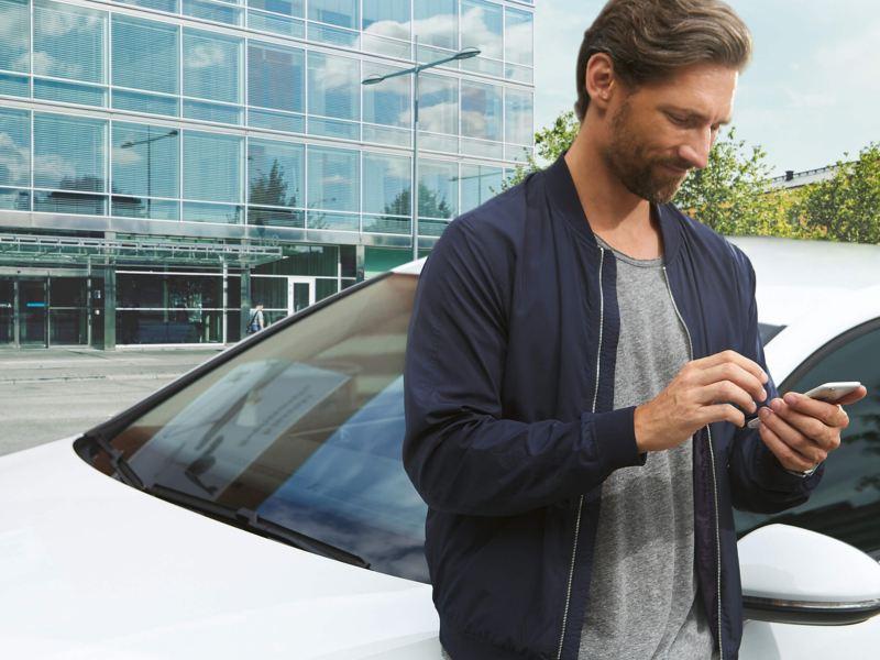A man using his smart phone app, next to a Volkswagen e-Golf.