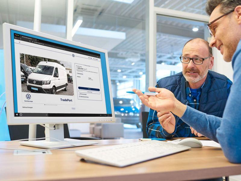 Ein TradePort Händler berät am PC einen Kunden.