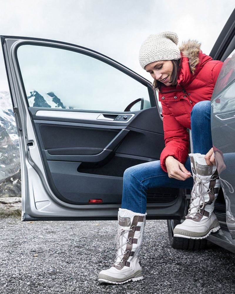 Woman sitting in vehicle lacing up winter boots