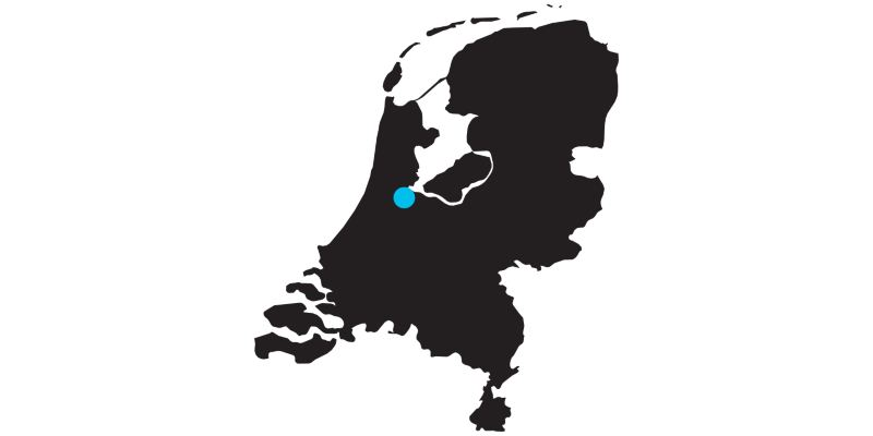 Outline of a map of the Netherlands with a mark on the location of Amsterdam