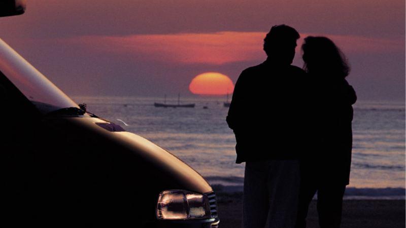 Para stoi na plaży z Volkswagenem Pojazdy użytkowe California i obserwuje zachód słońca.