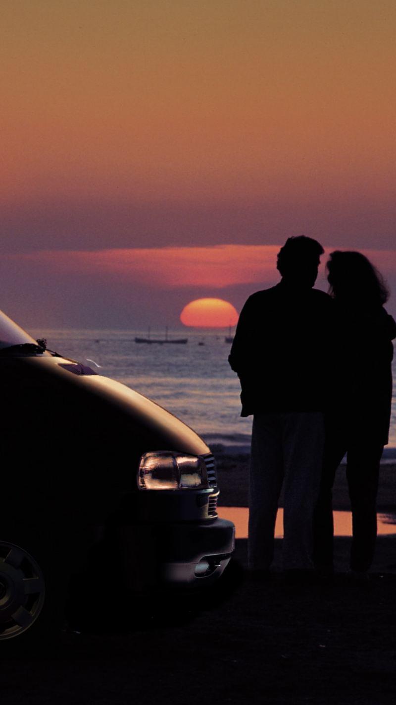 Ein Pärchen steht mit dem Volkswagen Nutzfahrzeuge California am Strand und betrachtet den Sonnenuntergang.