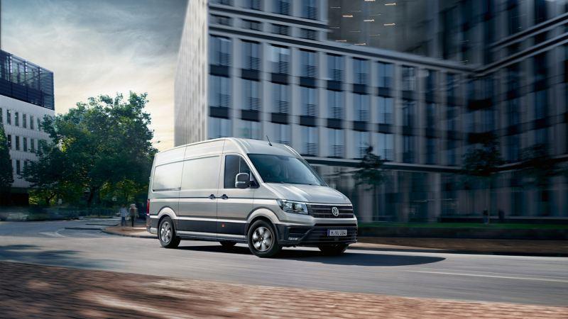 Volkswagen Crafter Furgon przejeżdża w miejskiej scenerii.
