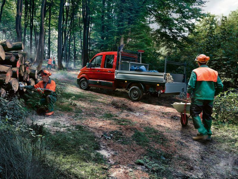 De  Crafter pick-up bedrijfswagen truck van Volkswagen staat op een smalle bosweg.