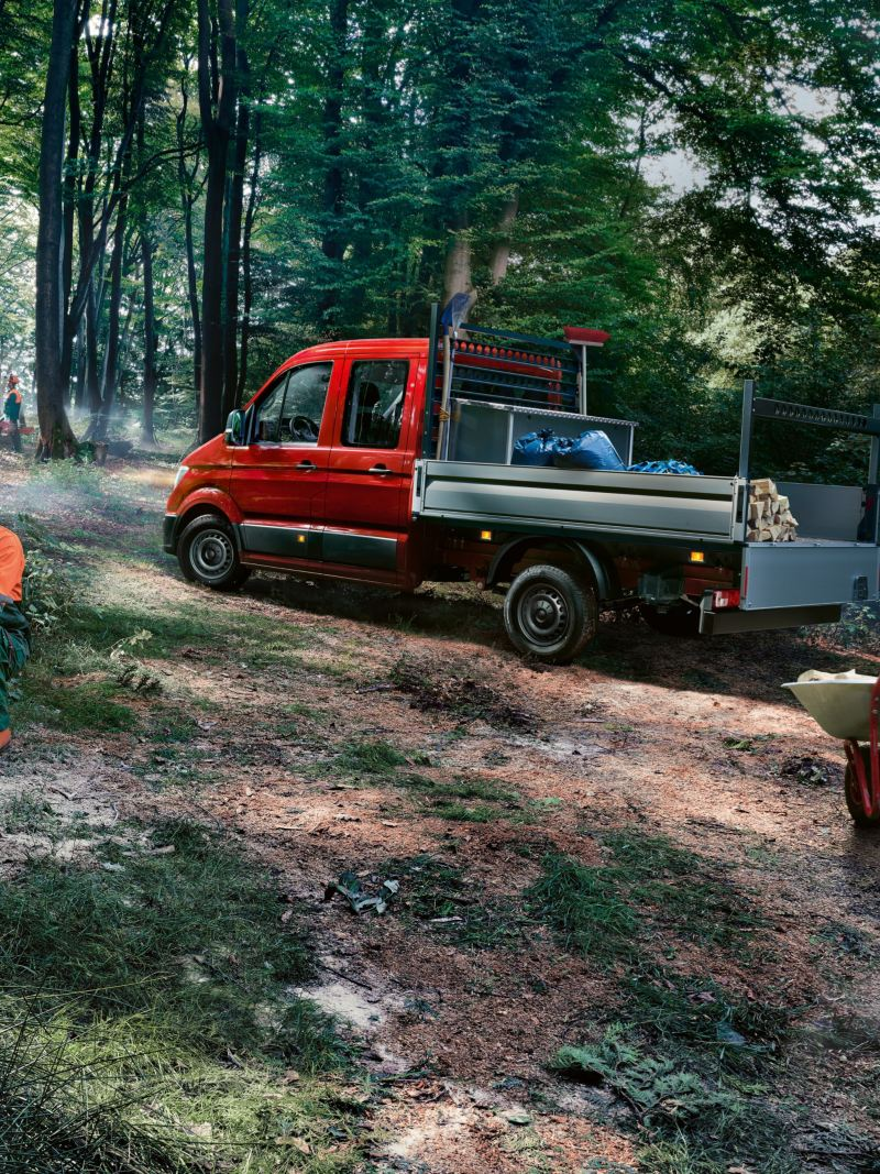 The Volkswagen Commercial Vehicles Crafter Dropside Van stands on a narrow forest path.