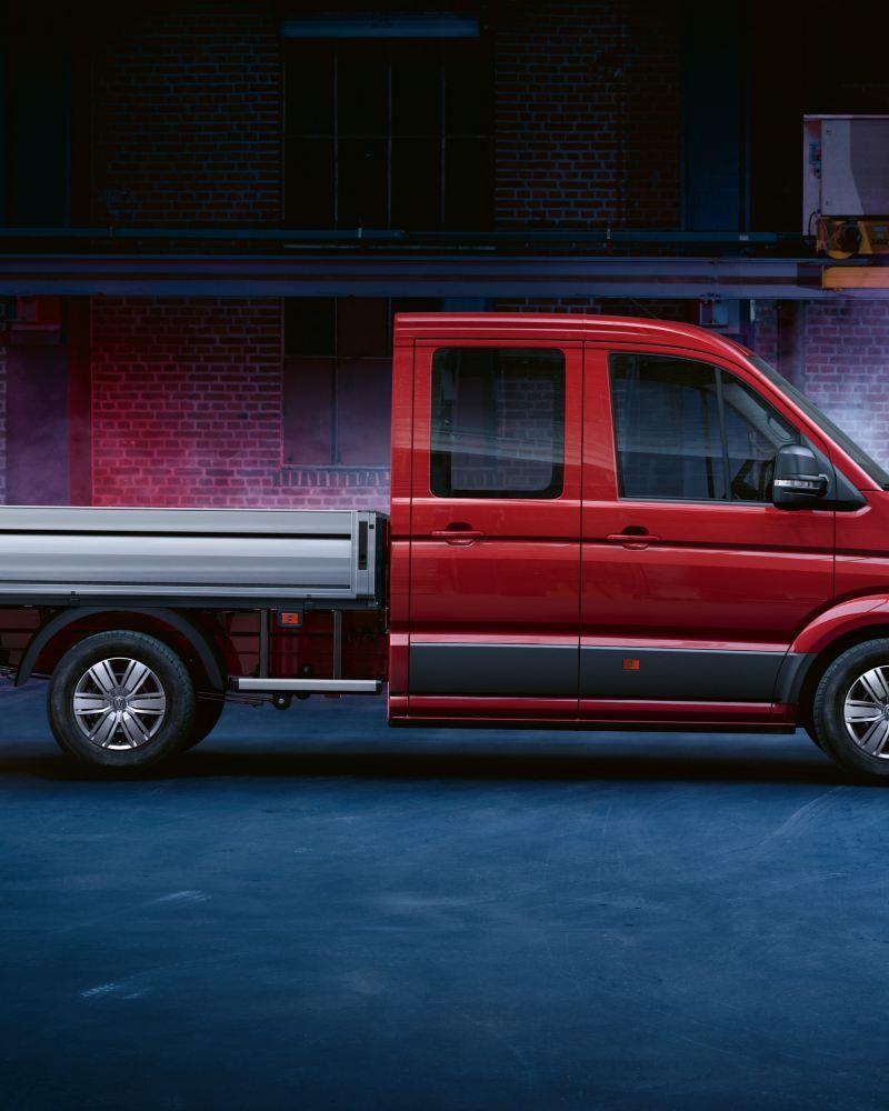Ein roter Crafter Pritschenwagen EcoProfi steht in einer Fabrikhalle.