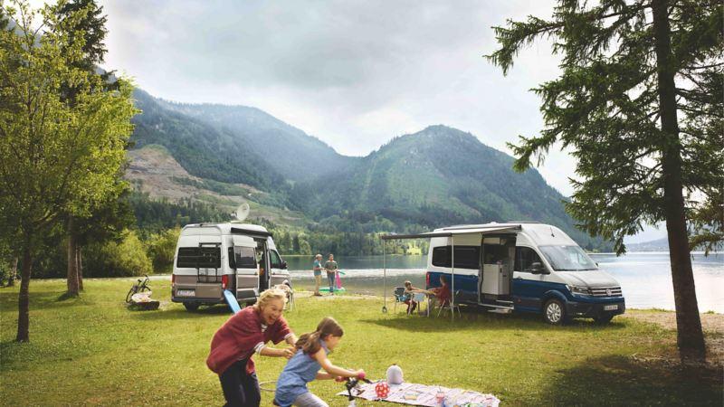 Grupa ludzi wypoczywająca nad jeziorem, w tle kampery Volkswagen