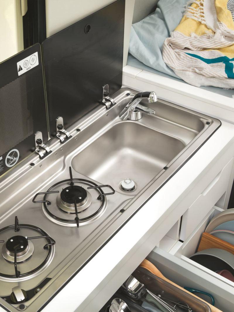 Le bloc kitchenette flexible du Grand California dans le détail. La protection vitrée est relevée et les tiroirs ouverts, de sorte que l'on peut voir la plaque de cuisson à gaz et l'espace de rangement pratique.