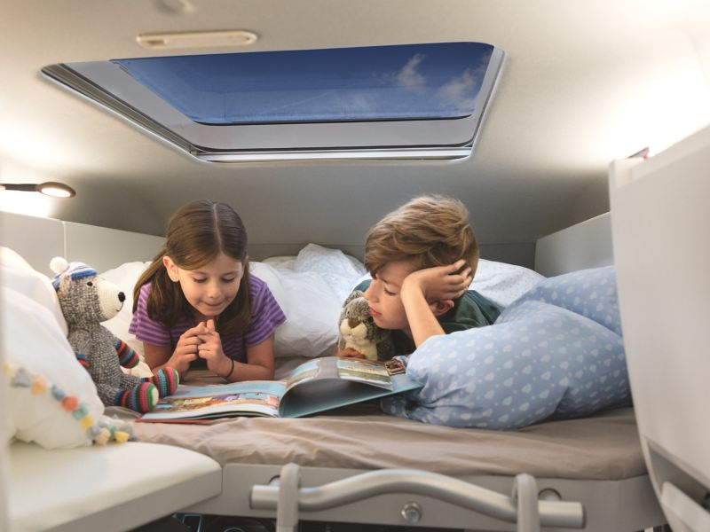 Two children are lying in the optional loft bed in the Volkswagen Grand California 600. They are reading a book together.