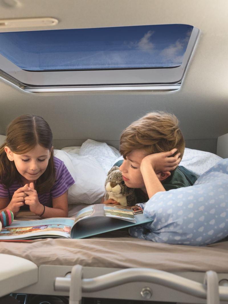 Deux enfants sont couchés dans le lit surélevé en option du Grand California 600. Ensemble, ils lisent un livre
