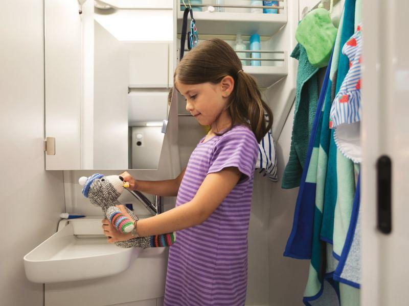 Une fillette est devant le lavabo du Grand California, elle lave les dents de son ours en peluche.