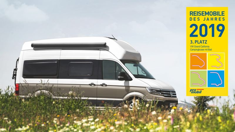 """The Grand California drives through a meadow of wild flowers. On the picture, we see the logo for """"Reisemobile des Jahres 2019"""" with a 1st place icon."""