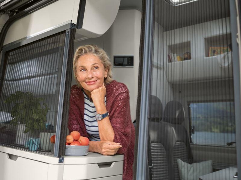 Kvinna vid fönster i VW Grand California husbil
