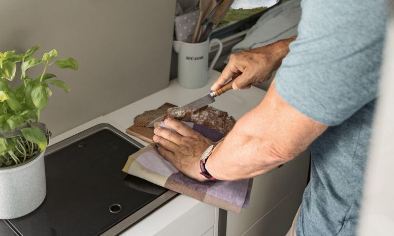 Man förbereder mat i VW Grand California husbil