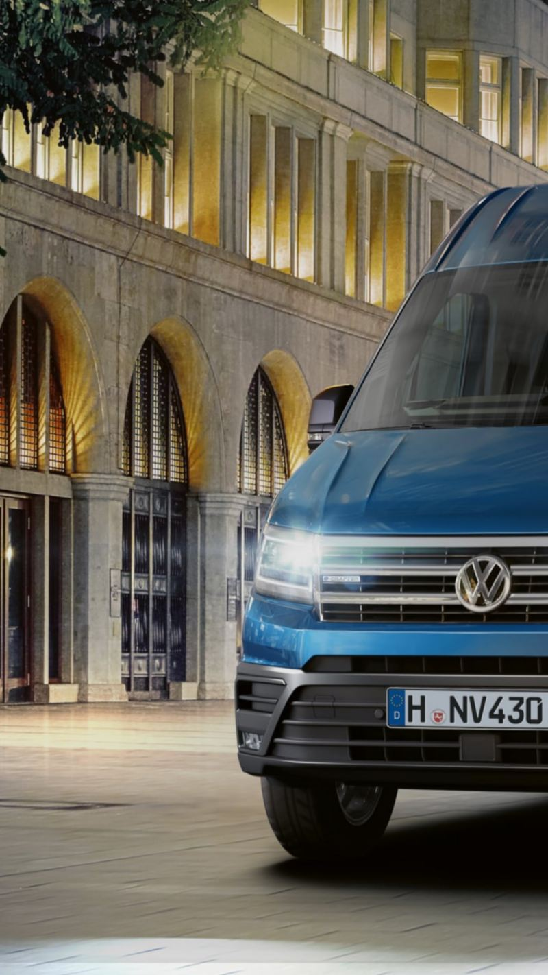 The e-Crafter drives through a brightly lit city in the dark.