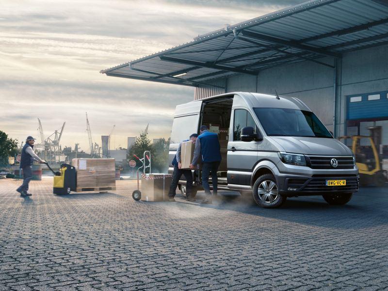 De Volkswagen bedrijfswagens Crafter bestelwagen voor een hal. Pakketten worden uitgeladen.
