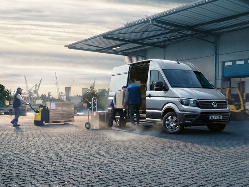 The Volkswagen Commercial Vehicles Crafter Delivery Van in front of a hall. Packages are being loaded inside.