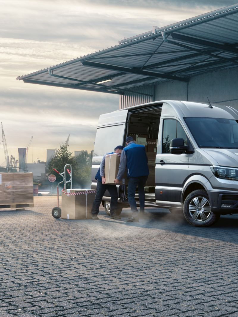 The Volkswagen Crafter Panel Van in front of a hall. Packages are being loaded inside.