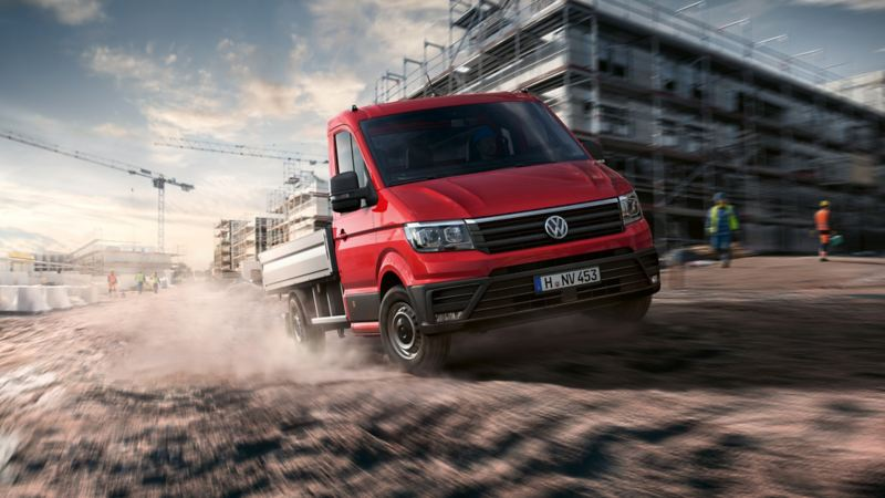 The Crafter Dropside Van drives quickly through a construction site.