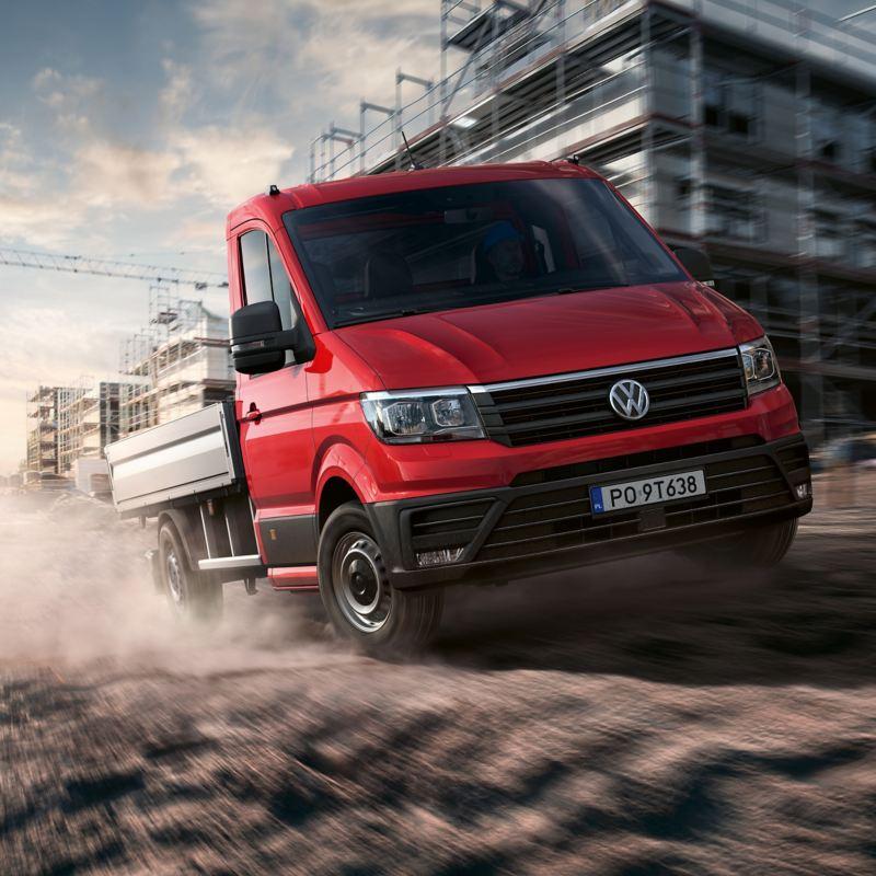 Volkswagen Crafter Skrzyniowy dynamicznie przejeżdża przez plac budowy.