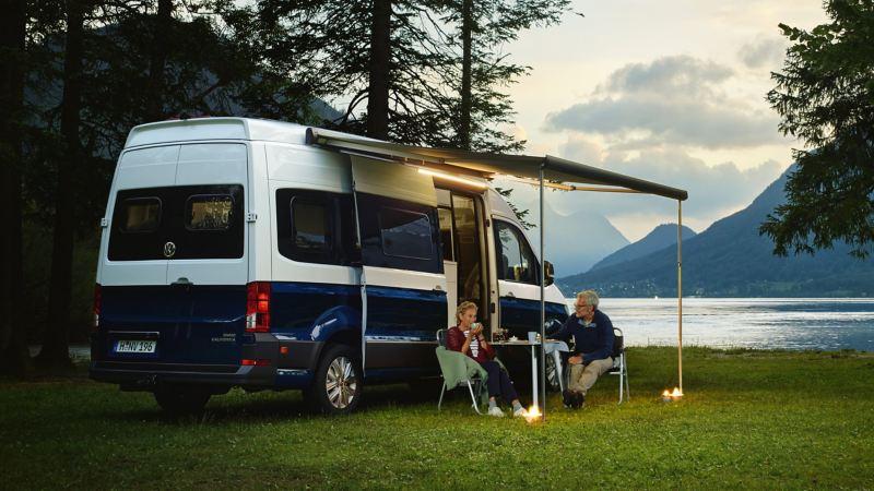 Le Grand California le soir, devant un lac de montagne. Un couple d'un certain âge est assis sous l'auvent, à la table de camping, et boit un thé, sous un éclairage agréable.