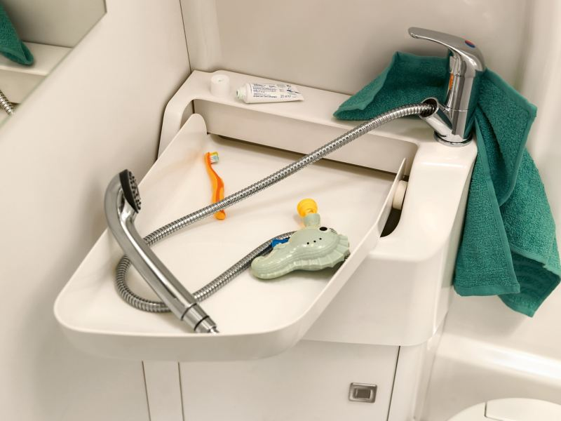 A close-up of the bathroom in the Volkswagen Commercial Vehicles Grand California. The flexible wash basin is folded out. It contains a shower head, a children's toothbrush and a colourful toy.