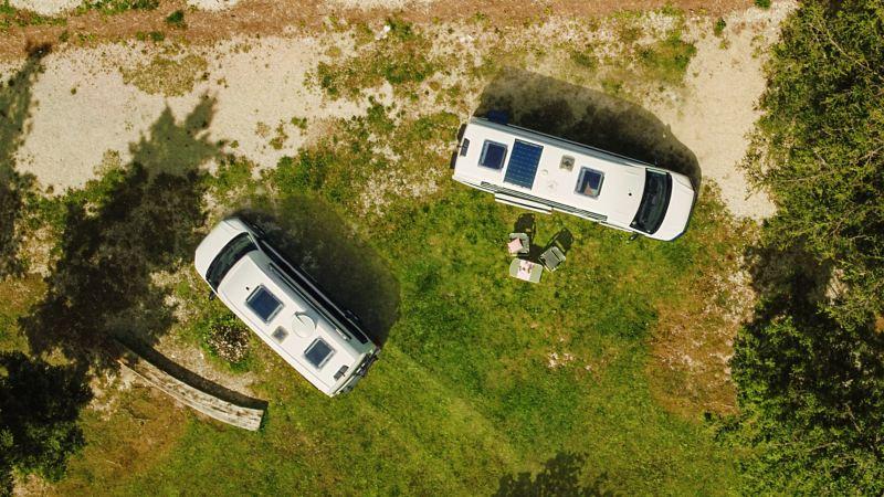 Vista dall'alto di due Grand California Volkswagen parcheggiati in un prato.