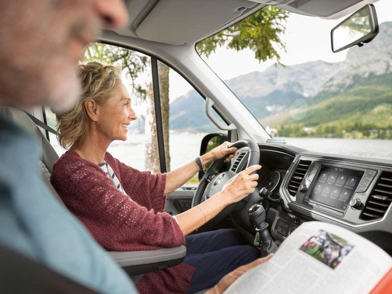 Vue dans la cabine de conduite du Grand California 680. Un couple d'un certain âge en voyage dans son camping-car.