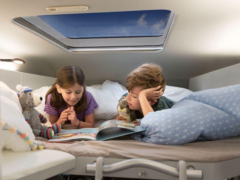 Zwei Kinder liegen im optionalen Hochbett des Grand California 600. Sie lesen gemeinsam ein Buch.