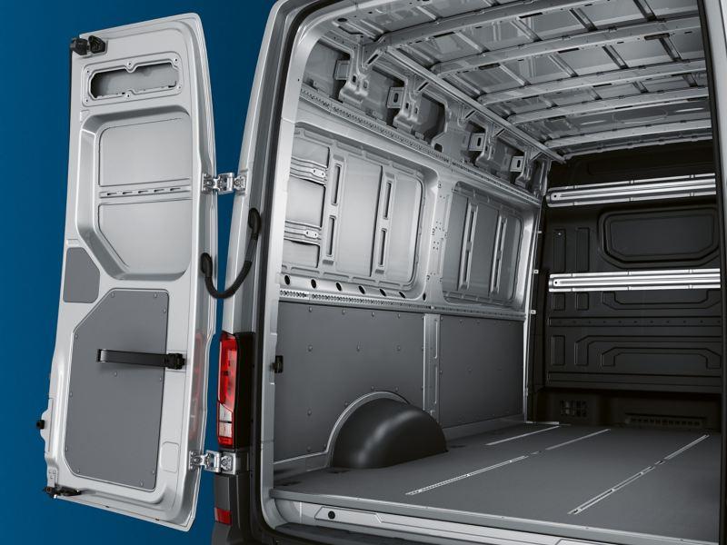 Volkswagen e-Crafter visto di 3/4 posteriore. Attraverso le porte posteriori a battente aperte è visibile il vano di carico.