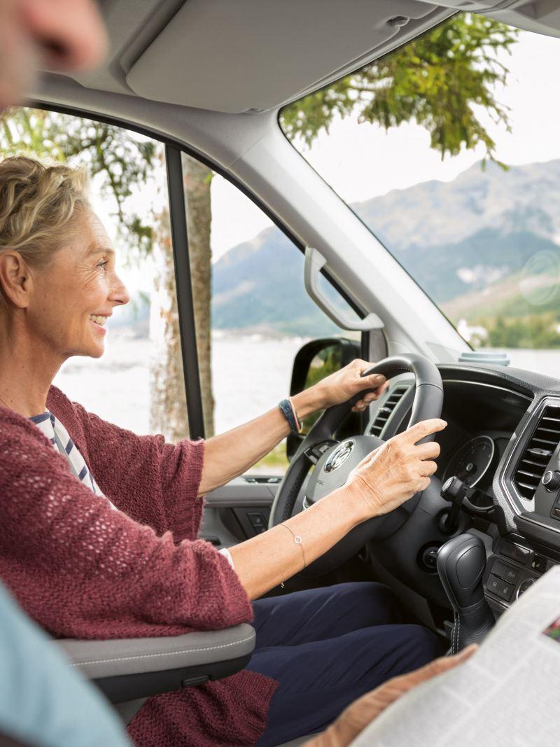 Blick in die Fahrerkabine des Grand California 680. Ein älteres Paar ist mit dem Reisemobil unterwegs.