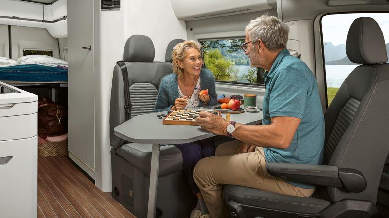 Um casal está sentado à mesa da autocaravana Volkswagen Grand California a jogar Damas e a petiscar.