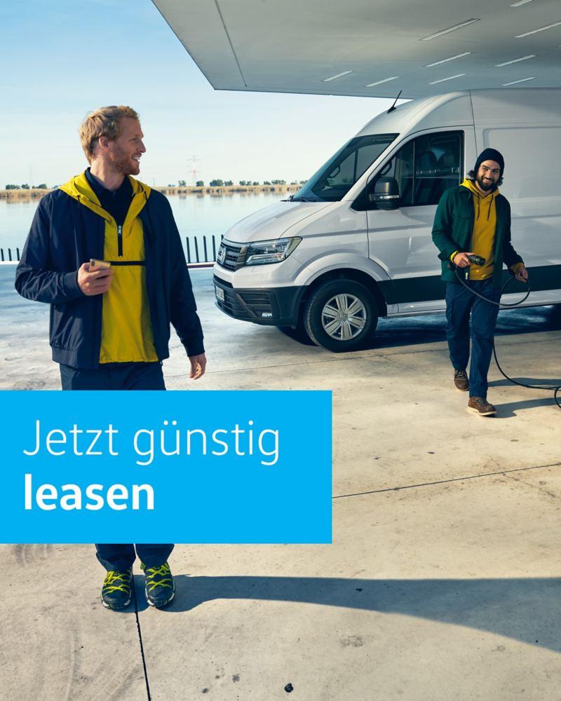 Der Volkswagen e-Crafter steht an einer e-Tankstelle mit Hafenblick.
