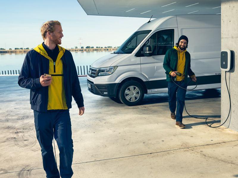 Volkswagen e-Crafter a una stazione di ricarica, sullo sfondo un'area portuale.
