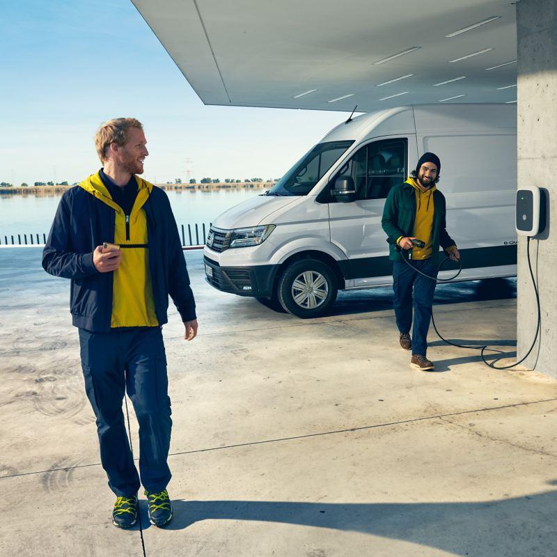 Un Volkswagen e-Crafter à une station de recharge dans une zone portuaire.