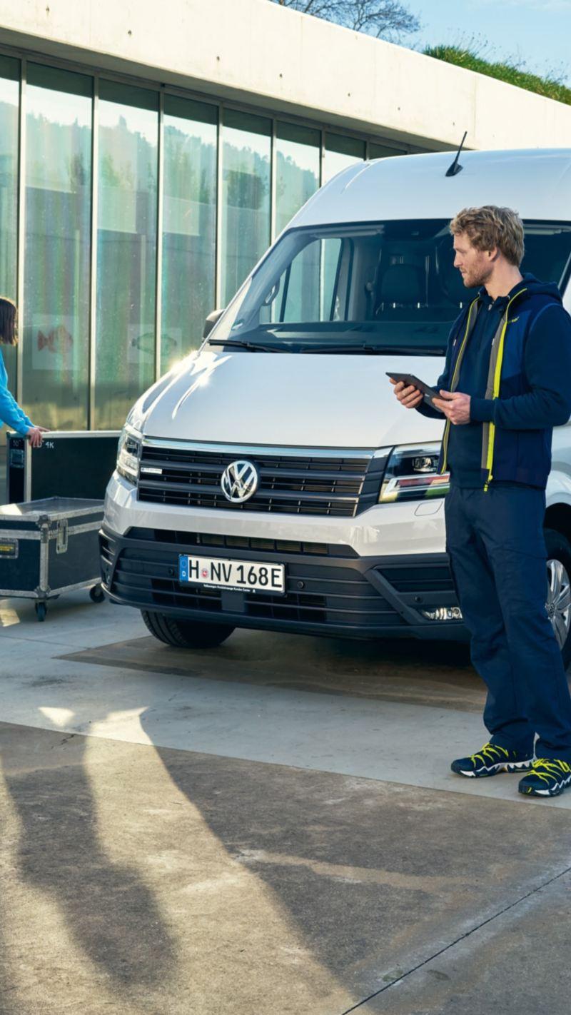 Ein Volkswagen e-Crafter steht in einer Alltagssituation an einer Ladestation.