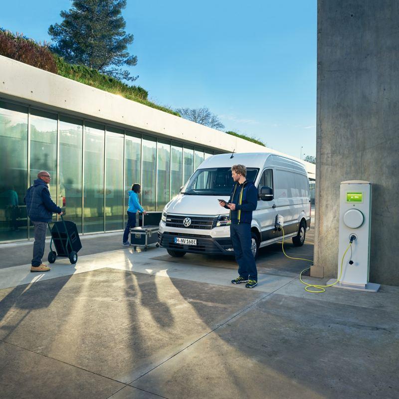 Un e-Crafter Volkswagen presso una stazione di ricarica in una situazione quotidiana.