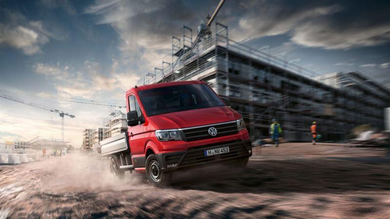 vw Volkswagen rød Crafter pickup med enkeltkabin og pickupplan kjører i fart over byggeplass med bygningsarbeidere i bakgrunn