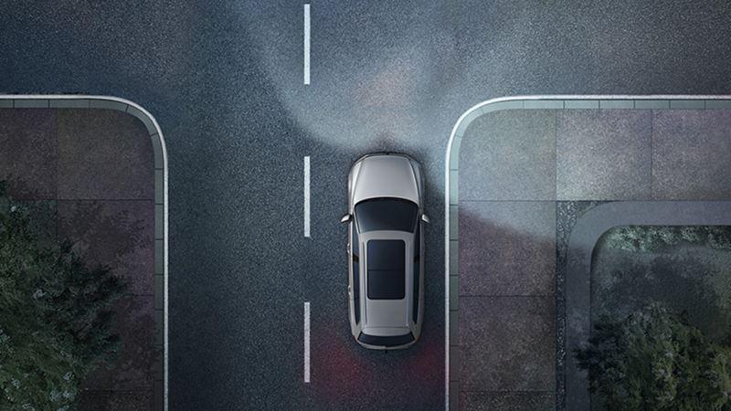 Volkswagen nocą na drodze widziany z góry. Widać światła przednie i doświetlanie zakrętów przez reflektory jako stożki światła.