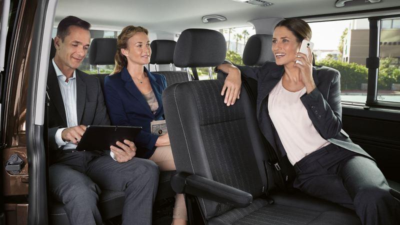 Zwei Frauen und ein Mann sitzen im Innenraum eines Fahrzeugs.
