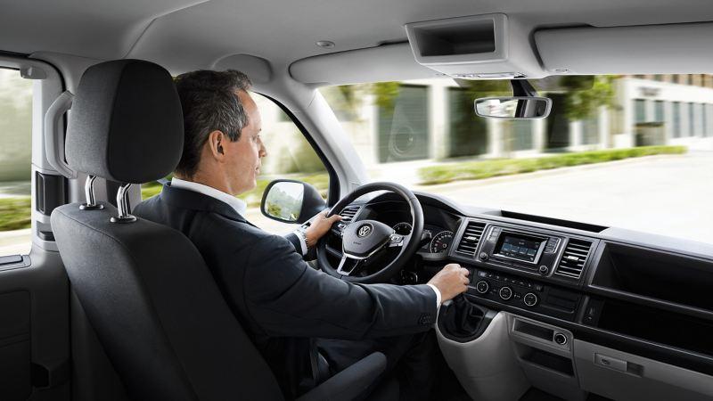 Kierowca za kierownicą Volkswagen T6 Caravelle.
