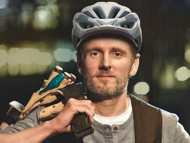 Ein Mann mit Fahrradhelm und geschultertem Werkzeug.