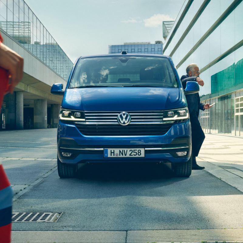 Ein VW Caravelle 6.1 in der Frontansicht, ein Mann lehnt sich an das Fahrzeug.