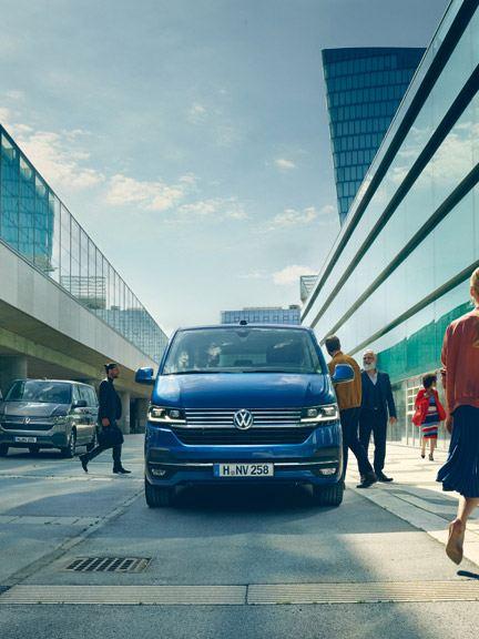 Volkswagen vw blå Caravelle varebil flyplass mennesker går på gaten by