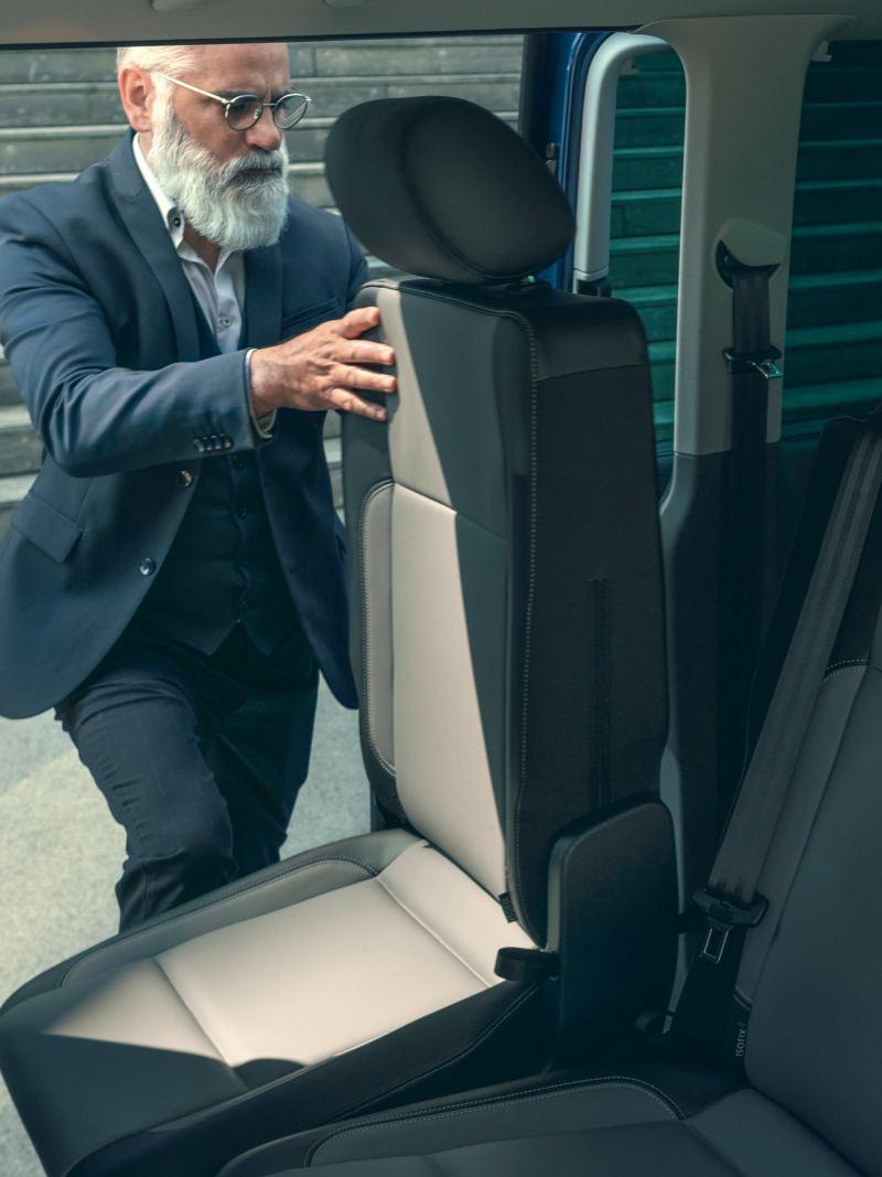 Mężczyzna ustawia siedzenie w przedziale pasażerskim Volkswagen Caravelle 6.1.
